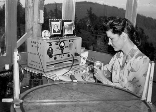 Fire lookout Thelma Duke operates radio at Chase Mountain lookout tower in Oregon.