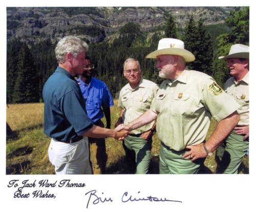 President Bill Clinton shakes hands with Chief Thomas. In the background, from left to right, are Brian Burke, Deputy Undersecretary of Agriculture, Richard Bacon, Deputy Regional Forester of Region 1, and Dave Garber, forest supervisor of the Gallatin National Forest. The photo was taken in August 1996 in Yellowstone National Park.